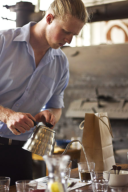 The barista, Dan, adding hot water to brew the grounds.